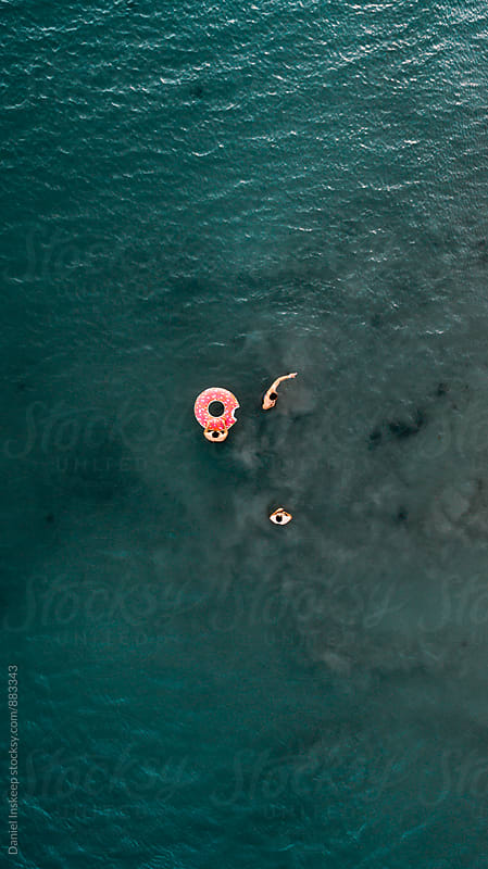 Swimming With a Donut Innertube in the Ocean by Daniel Inskeep for Stocksy United