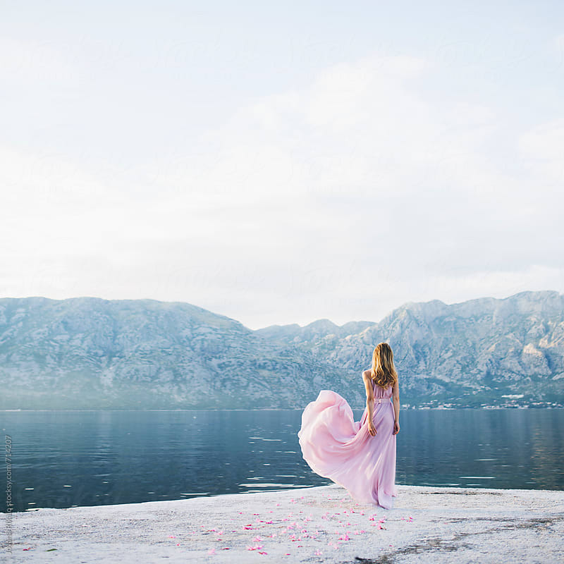 Back view of a woman in a pastel long dress standing on a dock by Jovana Rikalo for Stocksy United