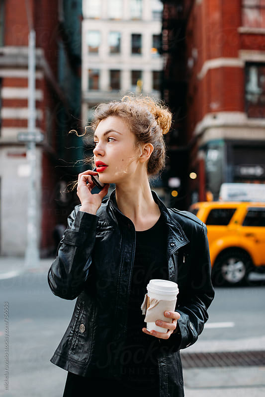 Attractive business woman calling with her cell phone in the street by michela ravasio for Stocksy United