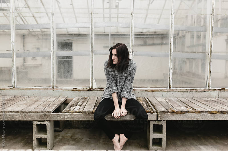 young woman sitting on wood pallets outside abandoned building by Nicole Mason for Stocksy United