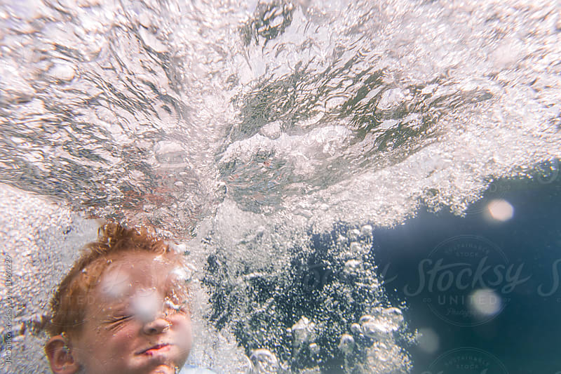 Underwater Face of Boy Jumping Into Summer Lake From Water Trampoline At Cottage by JP Danko for Stocksy United