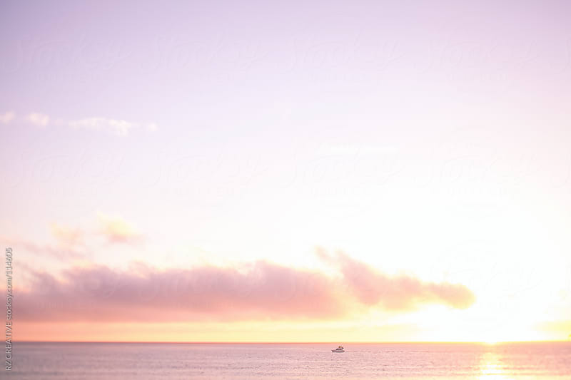 A boat cruising on the open ocean at sunset. by RZ CREATIVE for Stocksy United