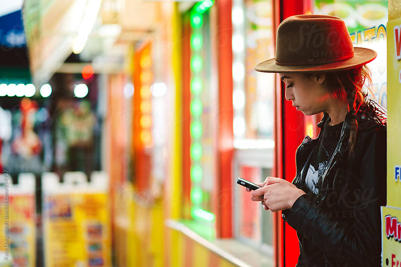 Trendy teenage girl on her smartphone outside a taco shop at night by Kate Daigneault for Stocksy United
