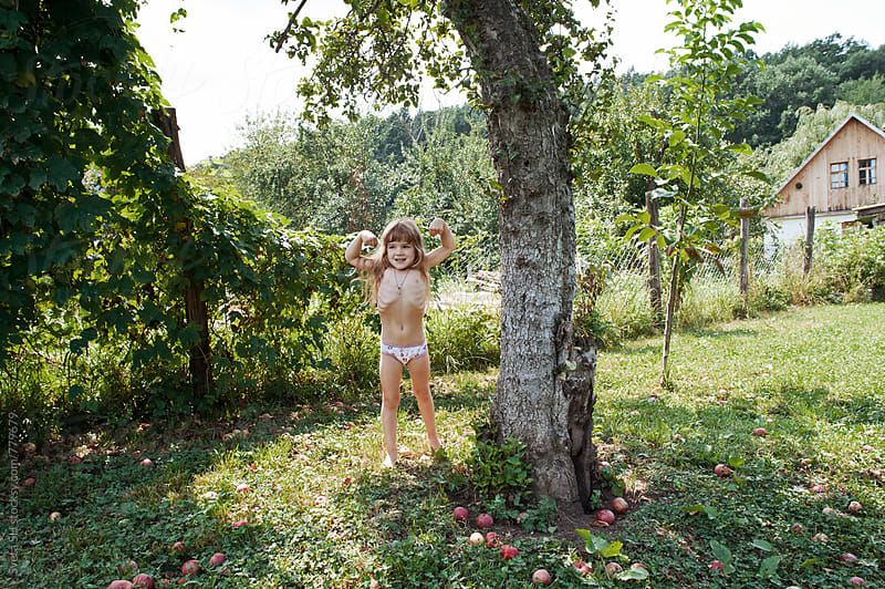 Little girl standing under an apple tree. by Sveta SH for Stocksy United