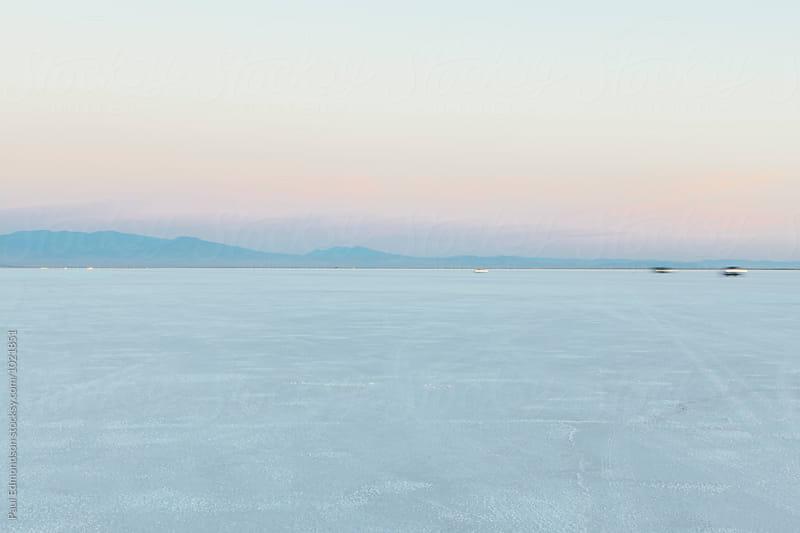 Cars driving across Bonneville Salt Flats at dawn, near Wendover, UT, USA by Paul Edmondson for Stocksy United