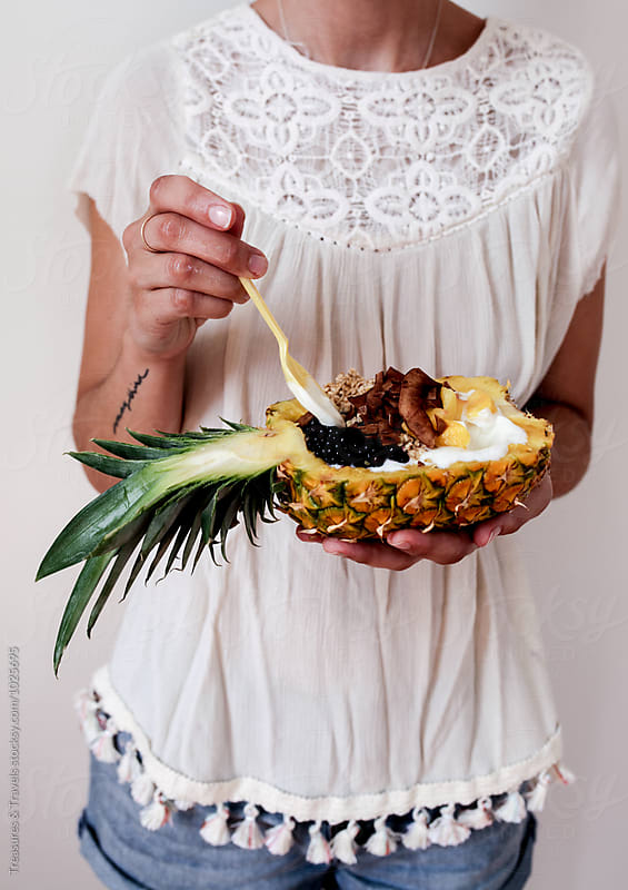 Young woman holding pineapple dessert by Treasures & Travels for Stocksy United