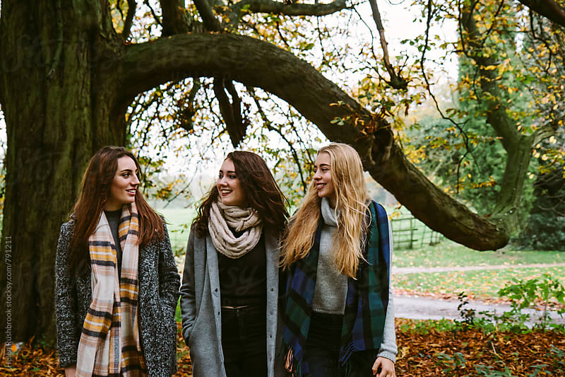 Three teenage friends walking outdoors in the countryside. by Helen Rushbrook for Stocksy United