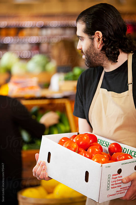 Market: Grocer Carrying Box of Tomatoes by Sean Locke for Stocksy United