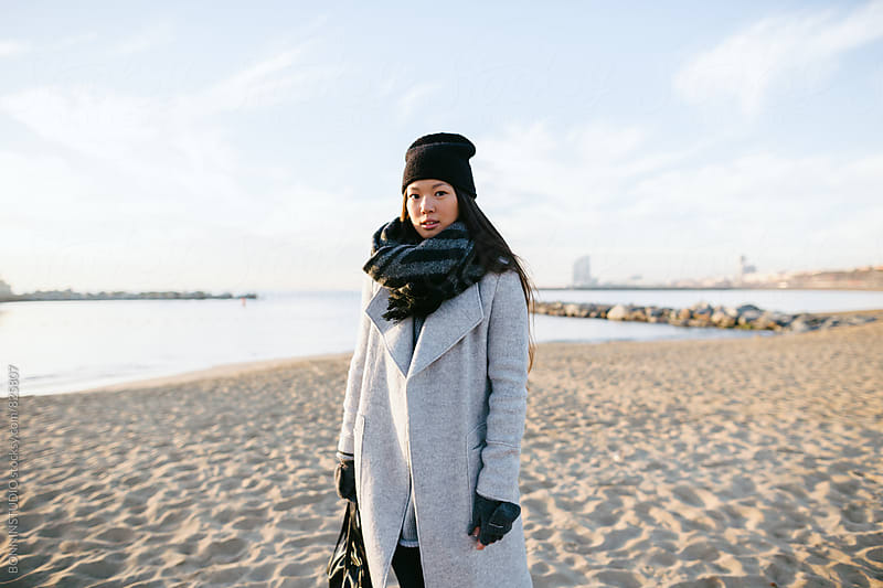 Chinese woman standing on the beach on winter. by BONNINSTUDIO for Stocksy United