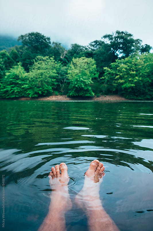 Feet in water in a forest lake by Micky Wiswedel for Stocksy United