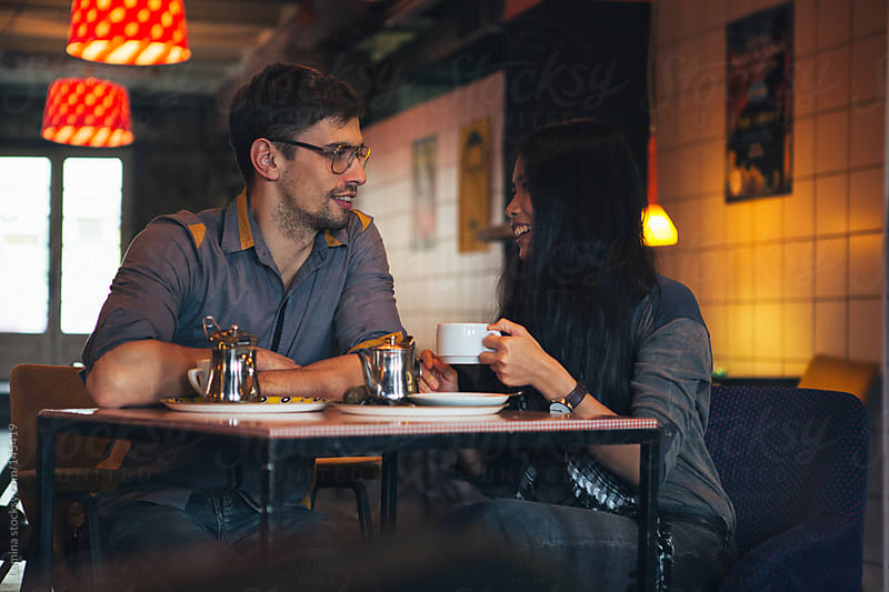 Multiethnic Couple Talking at a Cafe by Lumina for Stocksy United