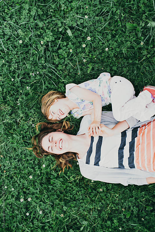 Laughter in the grass by Ali Lanenga for Stocksy United