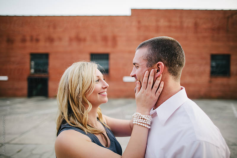 A beautiful couple in love standing in an urban warehouse area by Jakob for Stocksy United