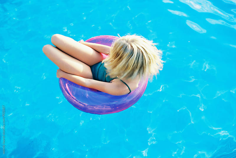teen girl with blonde short hair swinging her hair in pink floaty in blue swimming pool by wendy laurel for Stocksy United