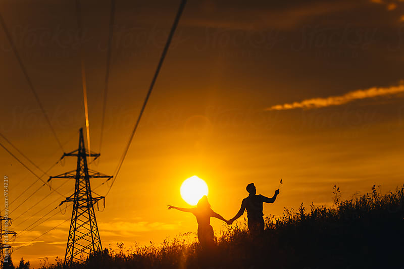 Silhouettes of couple walking under power lines by Evgenij Yulkin for Stocksy United