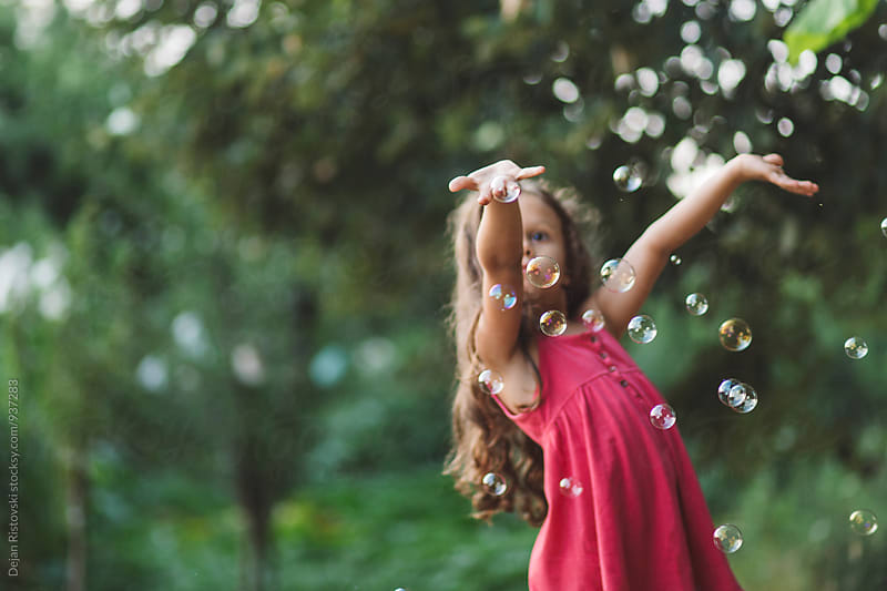 Little girl catching bubbles. by Dejan Ristovski for Stocksy United