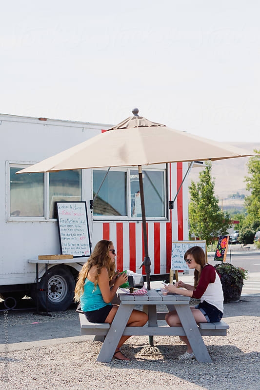Customers sit at picnic table outside food truck by Tana Teel for Stocksy United