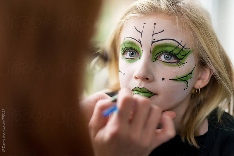 Mother Applying Face Paint Makeup for Little Girl Witch Halloween Costume by JP Danko for Stocksy United