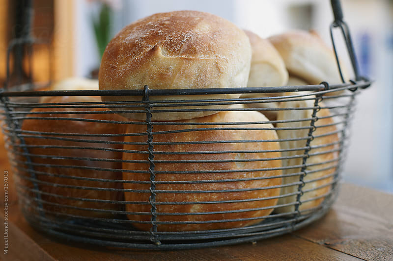 Fresh baked rolls in a basket by Miquel Llonch for Stocksy United