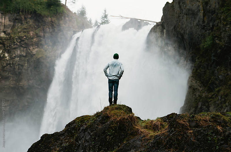 Young man standing in front of waterfall by Jesse Morrow for Stocksy United