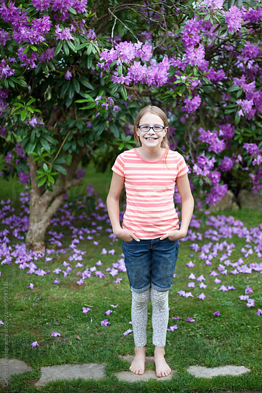 Eleven year old girl with glasses enjoying a fine spring day by Carleton Photography for Stocksy United