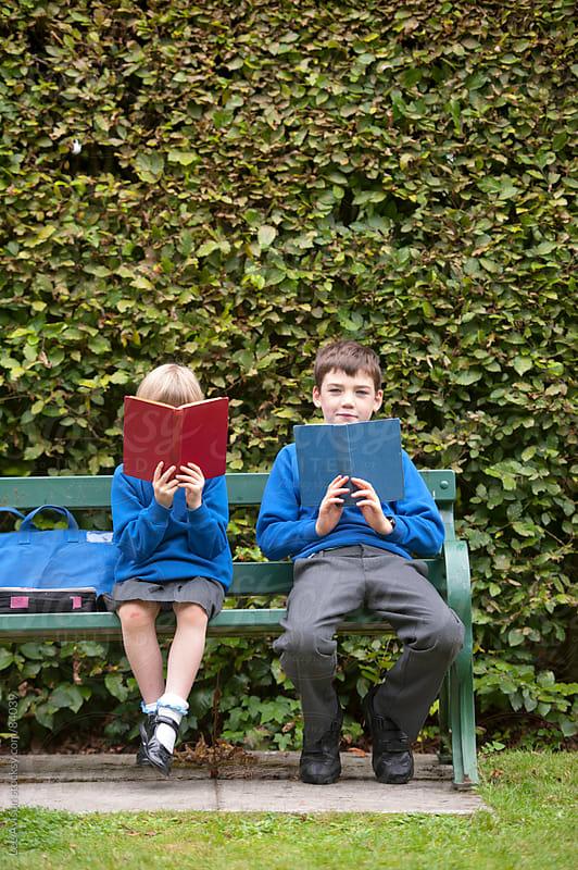 two children in school uniform reading books on a park bench by Lee Avison for Stocksy United