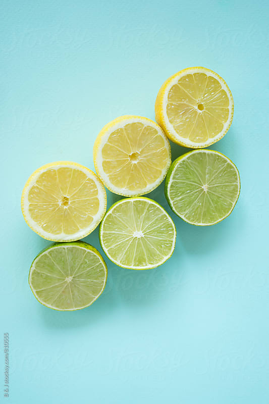 Lemons and limes on a pastel blue background by B & J for Stocksy United