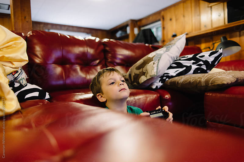 Young boy finding his comfort position while playing video games by Cameron Whitman for Stocksy United