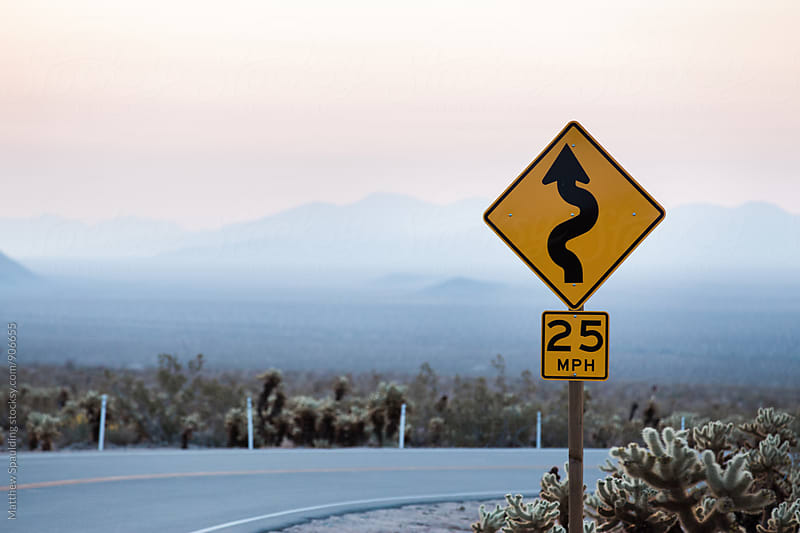 Sign for winding road in desert by Matthew Spaulding for Stocksy United
