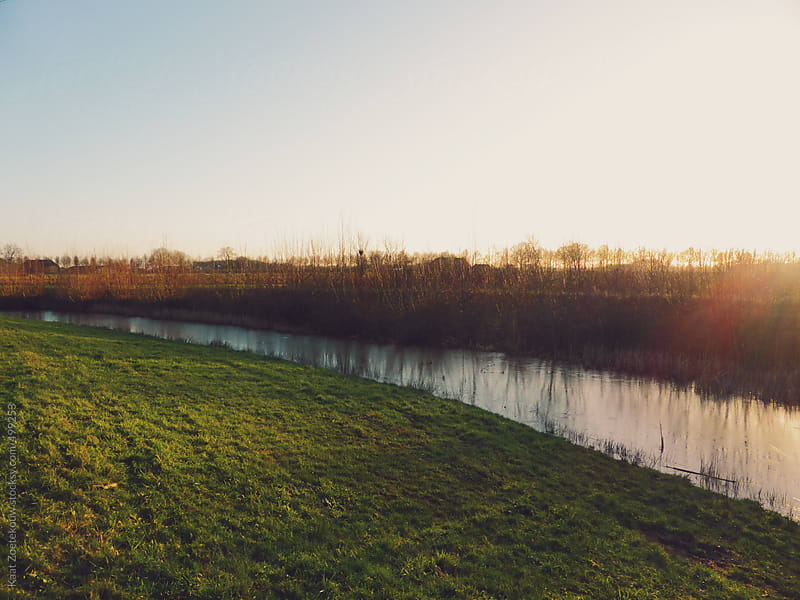 Sun sets over a small stream by Kaat Zoetekouw for Stocksy United