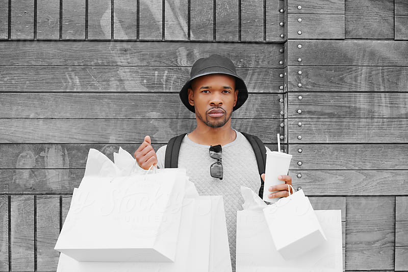 Funky Tracksuit Grey Shopping Man with his soda by Aila Images for Stocksy United