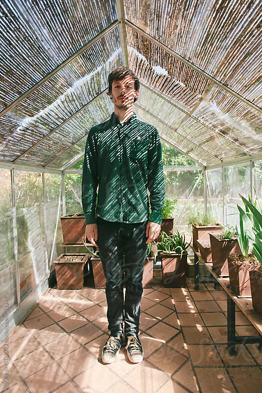 Young man standing on a greenhouse. by BONNINSTUDIO for Stocksy United