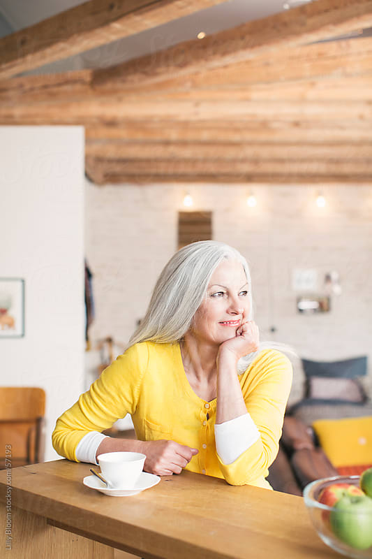 Senior woman in her living room with a cup of tea. by Lilly Bloom for Stocksy United