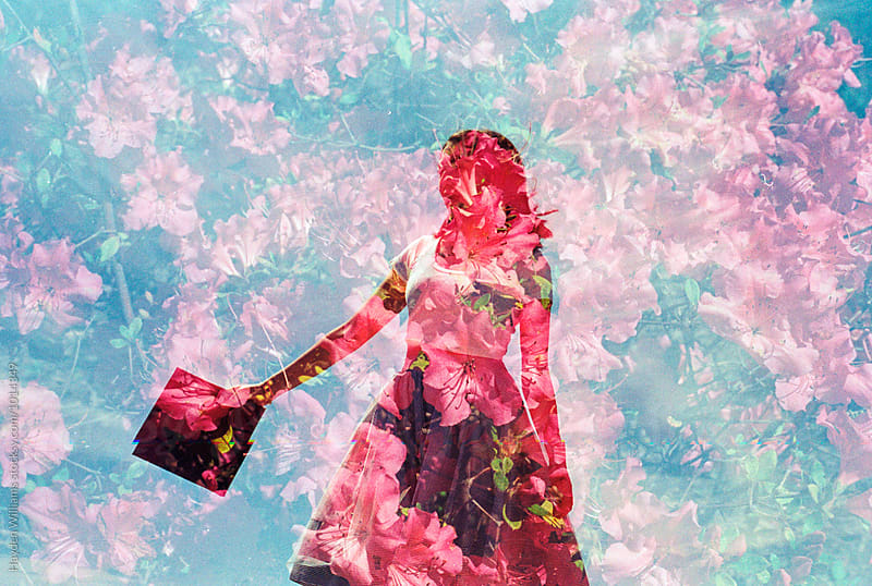 Double Exposure of young woman holding graduation cap in a field of red flowers by Hayden Williams for Stocksy United