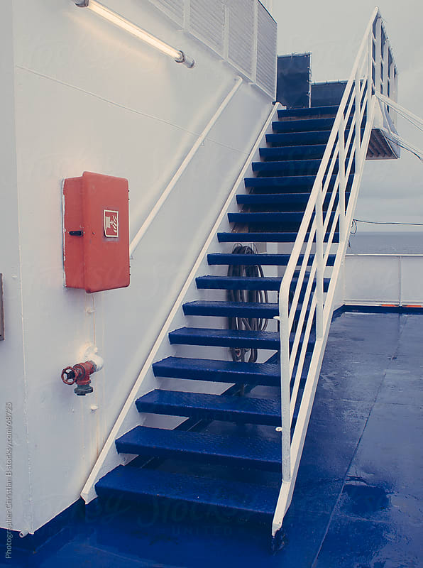 Stairs on ferry with red box by Photographer Christian B for Stocksy United