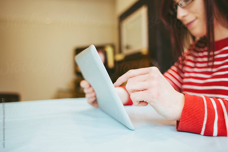 Young woman using a tablet by sally anscombe for Stocksy United