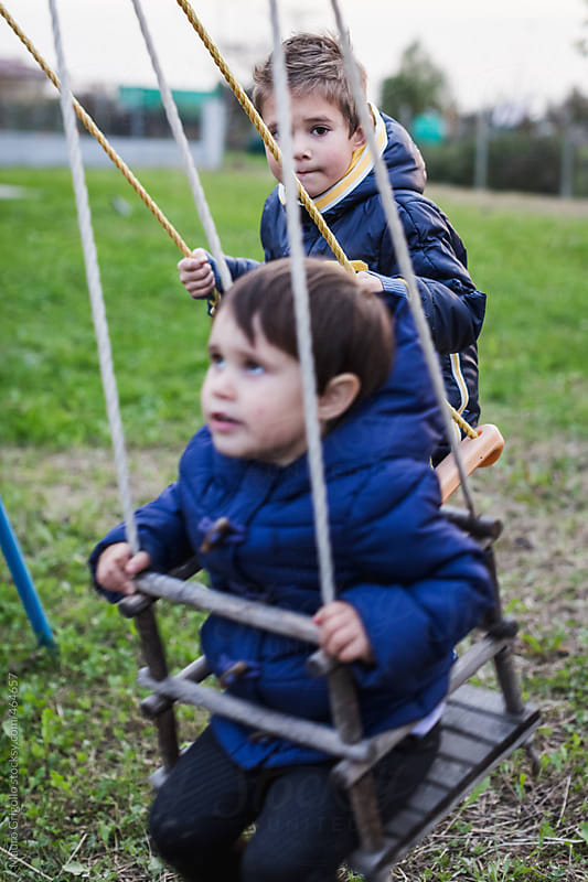 Children playing with swing by Mauro Grigollo for Stocksy United
