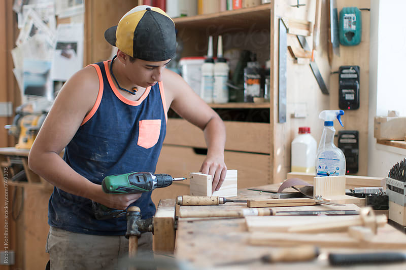 Young carpenter working in workshop by Robert Kohlhuber for Stocksy United