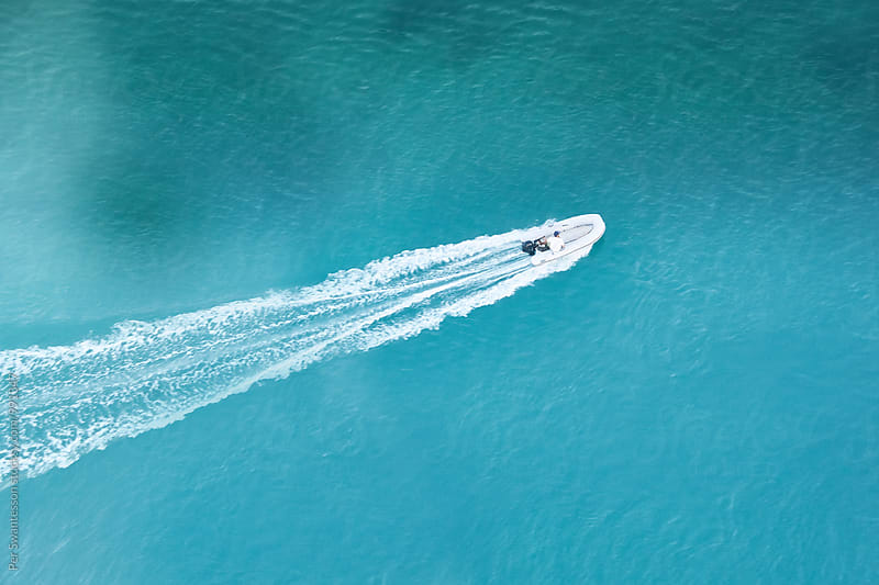 Speedy dinghy boat on turquoise waters by Per Swantesson for Stocksy United