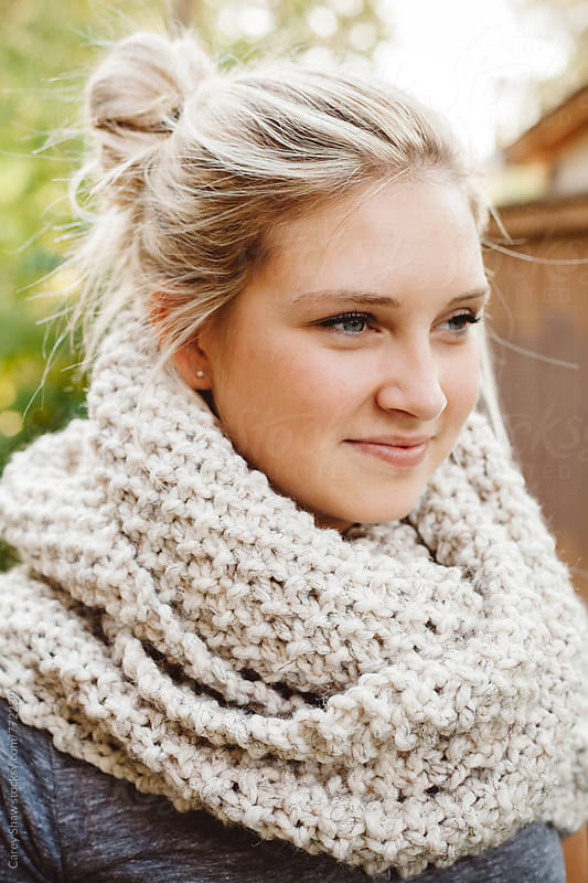 Beautiful young woman wearing cream knit scarf by Carey Shaw for Stocksy United