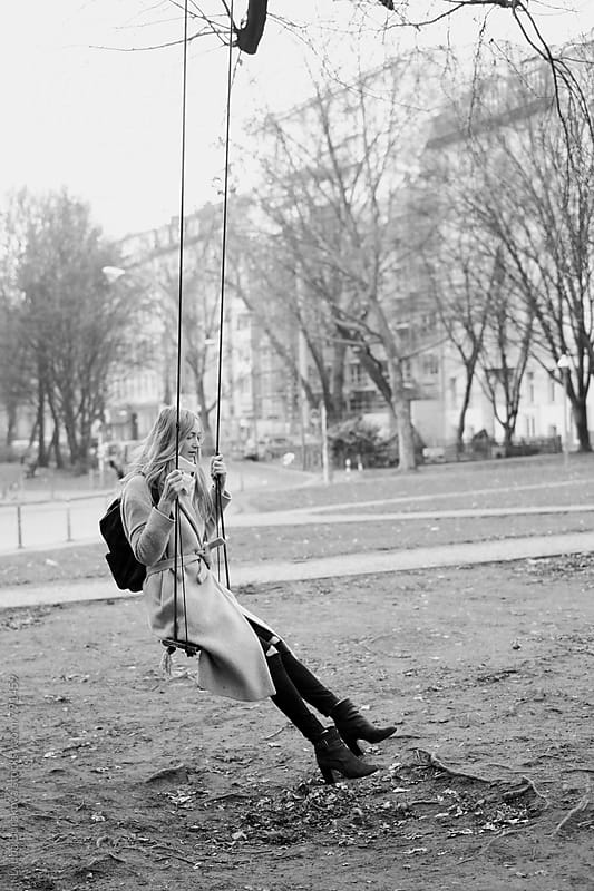 Young woman on a swing outdoors by Lyuba Burakova for Stocksy United