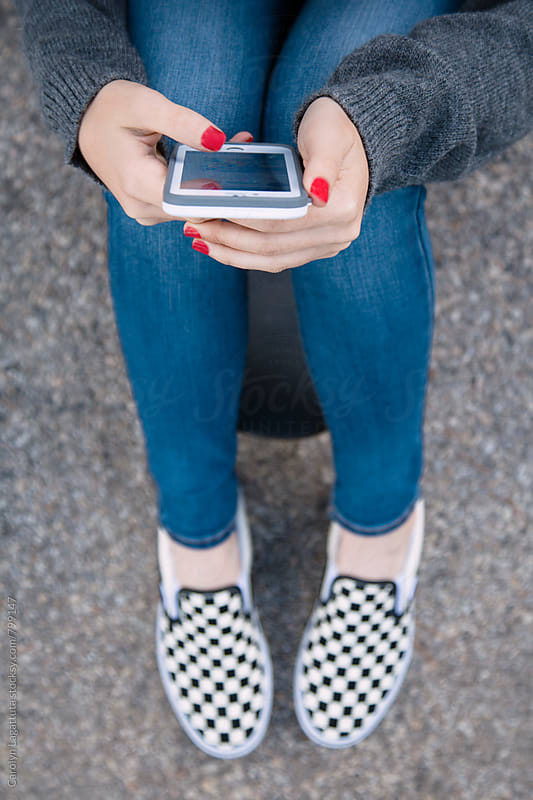 Teenage girl sitting on her skateboard and looking at her phone by Carolyn Lagattuta for Stocksy United