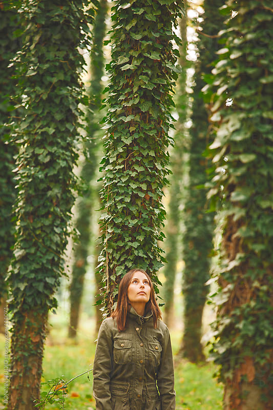 Young woman looking up on an autumnal forest. by BONNINSTUDIO for Stocksy United