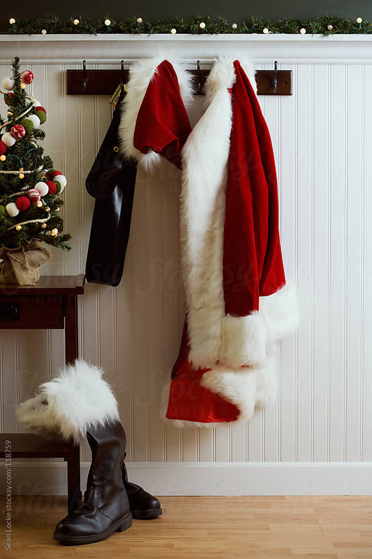 Christmas: Santa's Coat and Boots Hanging in Hall by Sean Locke for Stocksy United