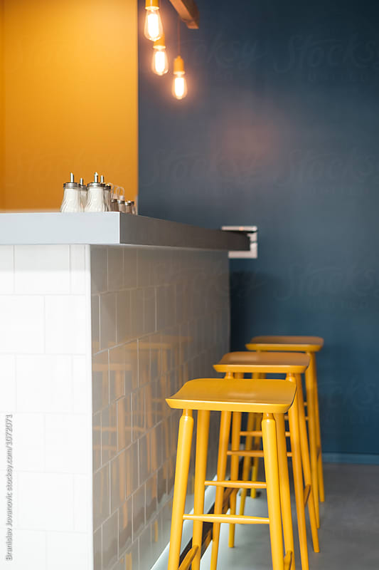Bar Counter with Yellow Chairs at the Restaurant by Branislav Jovanović for Stocksy United