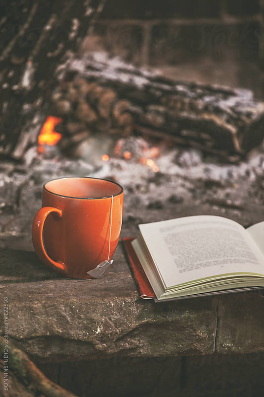 A hot cup of tea and book in a fireplace. by BONNINSTUDIO for Stocksy United