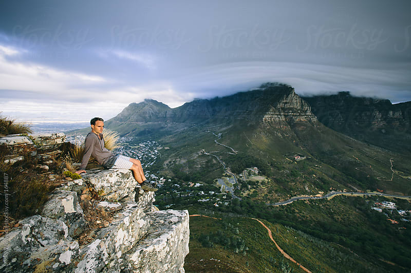 Hiker resting and enjoying the view with Table Mountain in the background by Micky Wiswedel for Stocksy United
