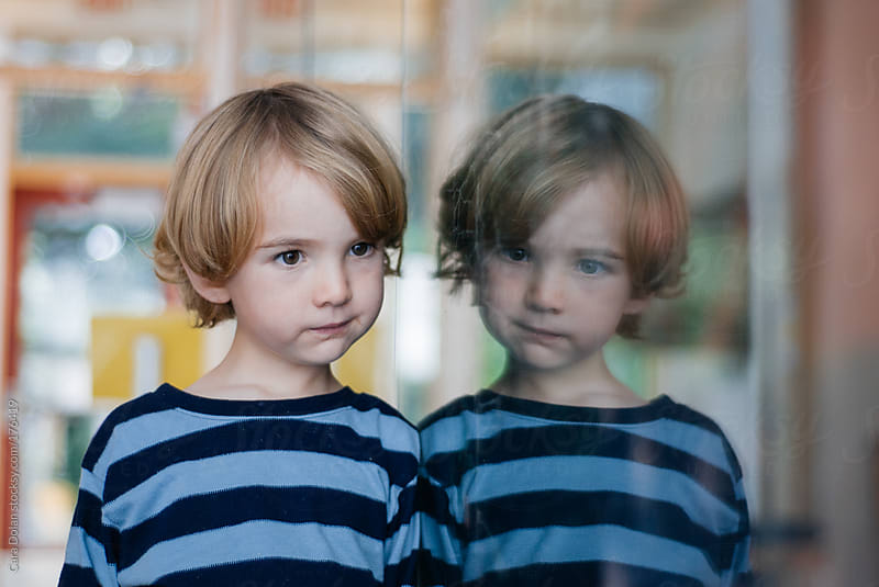 Young boy is reflected in a window by Cara Dolan for Stocksy United