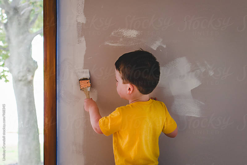 Little boy painting a wall by Lindsay Crandall for Stocksy United