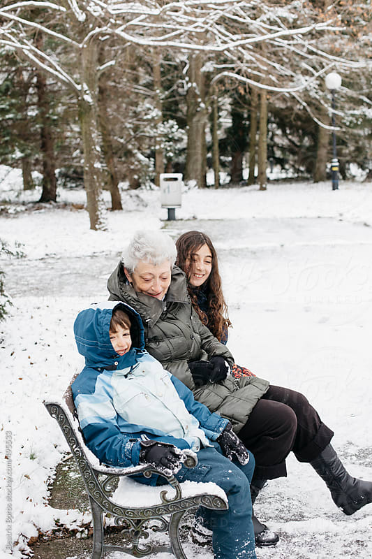 Side view of a grandma and grandkids sitting happily on a bench outdoors in Winter by Beatrix Boros for Stocksy United